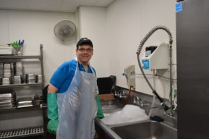 Bryan smiles at the camera while on duty at his dish washing job. He wears an apron and long rubber gloves while standing at a sink full of suds.