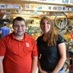 Aaron stands next to Sarah in the bike shop.