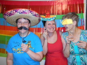 Kaitlyn poses with two of the individuals she supports. They are in a photo booth with fiesta-themed photo props.