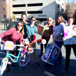 Staff smile as they prepare to distribute large gifts including a bike.