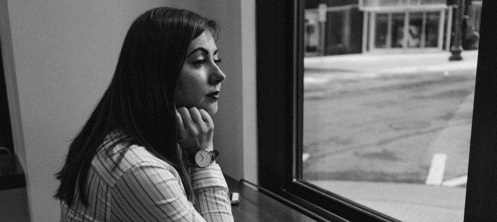 A young woman staring out a window.
