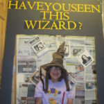 Woman wears wizard hat smiles for photo contest.